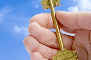 Golden Key In A Hand Against Blue Sky